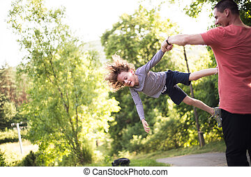 Young father spinning his son. Sunny summer nature.