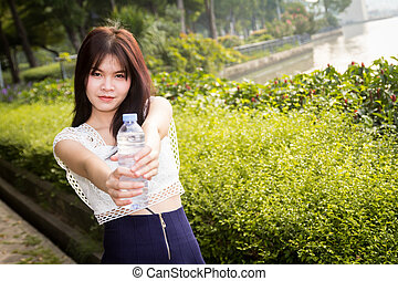 Young beautiful woman wearing white shirts drinking water at...