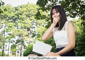 Young woman reading a book in garden