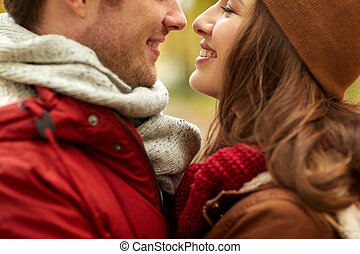 close up of happy young couple kissing outdoors - love,...