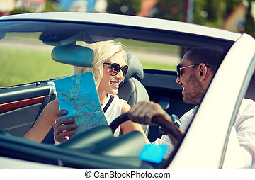 happy man and woman with map in cabriolet car - road trip,...
