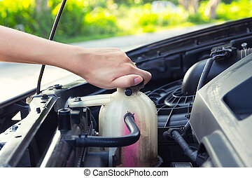 Coolant car check - Asian girl's hand checking level of...