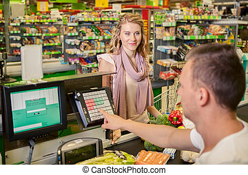 Woman buying food at supermarket and making check out with...