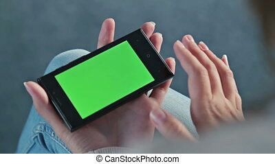 Female touching greenscreen mobile phone and scroll pages -...