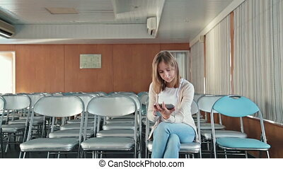 Woman uses her new digital PC tablet in the empty conference hall