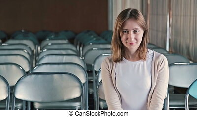 Happy young woman applauding in the empty conference hall of...