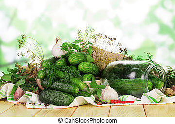 Pile fresh cucumbers in glass jar, spices on abstract green....
