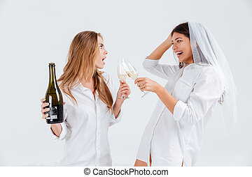 Two happy girlfriends celebrating engagement with veil and...