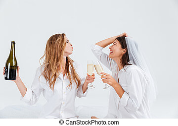 Two smiling women wearing bridal veil and holding champagne...