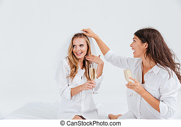 Two attractive women celebrating wedding with champagne...