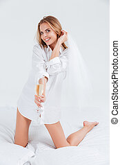 Smiling woman holding glass of champagne and looking at camera