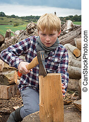 Young Woodcutter Chopping a Piece of Firewood with An Axe