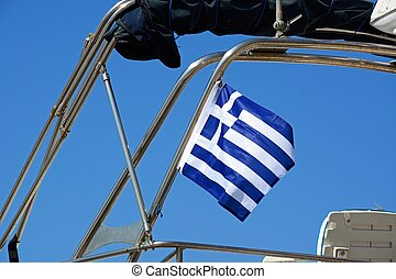 Greek flag on a motor boat against a blue sky. - Greek flag...
