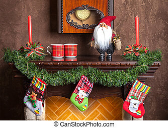 Christmas decoration of fireplace candles, garland and socks.