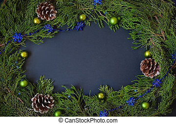 Border, frame from christmas tree branches with pine cones and blue berries