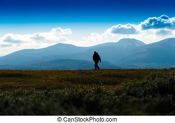 Shadow of lonely traveller in Norway background
