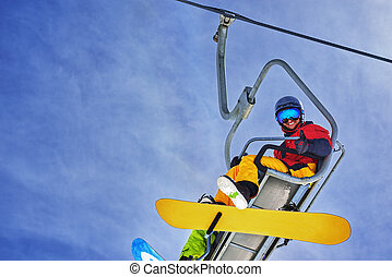 Snowboarder sitting on chairlift and smiling, close-up -...