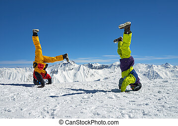 Two snowboarders are on hand upside down in high mountains -...