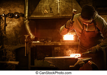 Blacksmith forging the molten metal on the anvil in smithy.