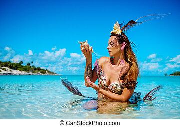 Portrait of exotic fantasy mermaid in blue ocean.