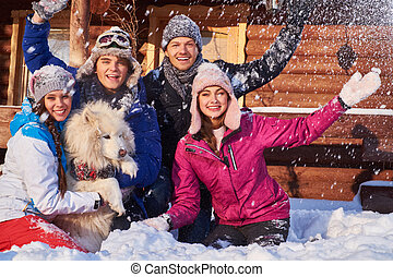 Cheerful friends with dog spend winter holidays together at...