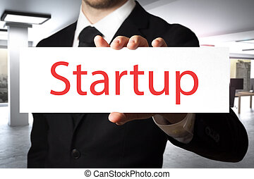 businessman holding sign startup - businessman in office...