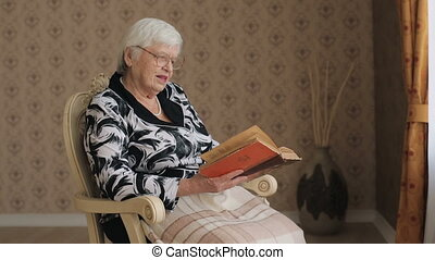 Old woman reading book at home