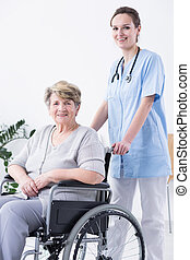 Nurse and woman on a wheelchair - Young female nurse...