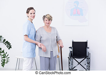 Smiled elder woman with cane, supported by her female nurse