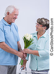 Old man giving flowers to woman with walking frame