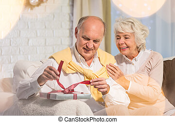 Senior man unwrapping christmas gift - Happy woman and...
