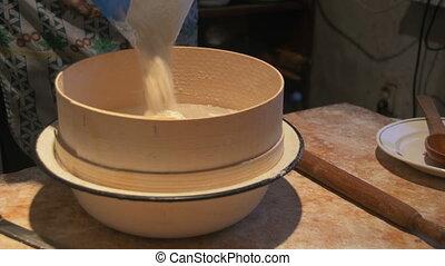 woman sifts the flour through a sieve .