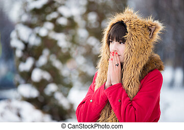 Woman shivering from cold outdoors in wintertime - Portrait...
