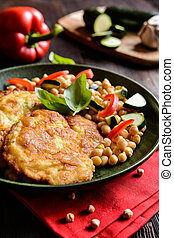 Roasted pork cutlets coated in cheese and breadcrumbs, served with chick peas and vegetable