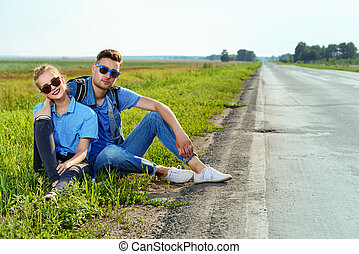 happy couple by a road - Hitchhiking couple. Happy young...