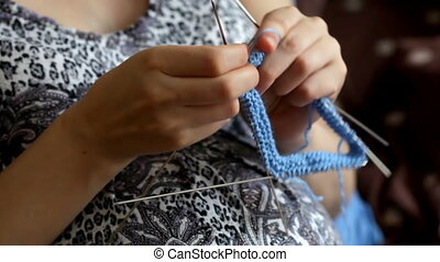 Pregnant woman crocheting for baby during pregnancy....