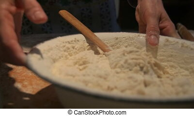 Woman is making dough - Woman stir with a wooden spoon raw...