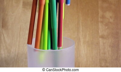 bright felt-tip pens fall in a glass, slow motion,