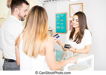 Couple buying jewelry with a credit card