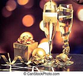 Glasses with champagne against holiday lights