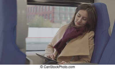 Business woman on the train running on the tablet, raw video