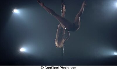 View of beautiful young woman dancing on pylon in studio