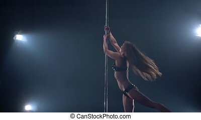 View of beautiful female dancer rotating on pole in studio