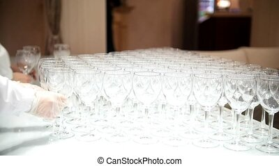 Waiter puts a lot of empty glasses on white table cloth,...