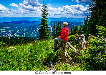 Senior Woman resting on a tree stump during a hike through the mountain alpine meadows with wild Flowers on Tod Mountain