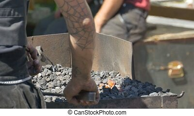 Blacksmith Arranges Coals - Blacksmith arranges the coals in...