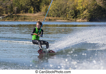 Young Wakeboarder Performing Tricks - A young athlete wake...