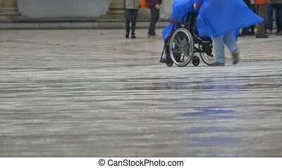 Man in a Wheelchair in Rain - Man in a wheelchair is...