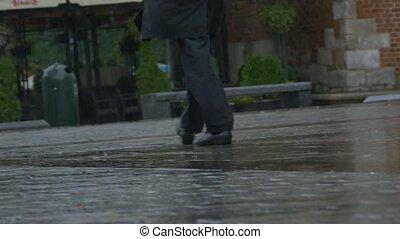 Man Walking Through Rain - Man wearing a black suite is...