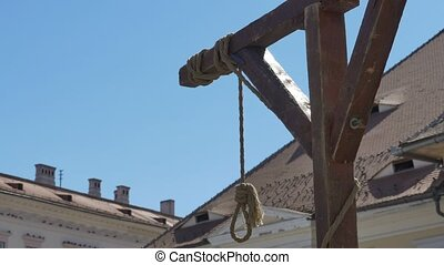 Hanging with Blue Sky - A medieval hanging swinging gently...